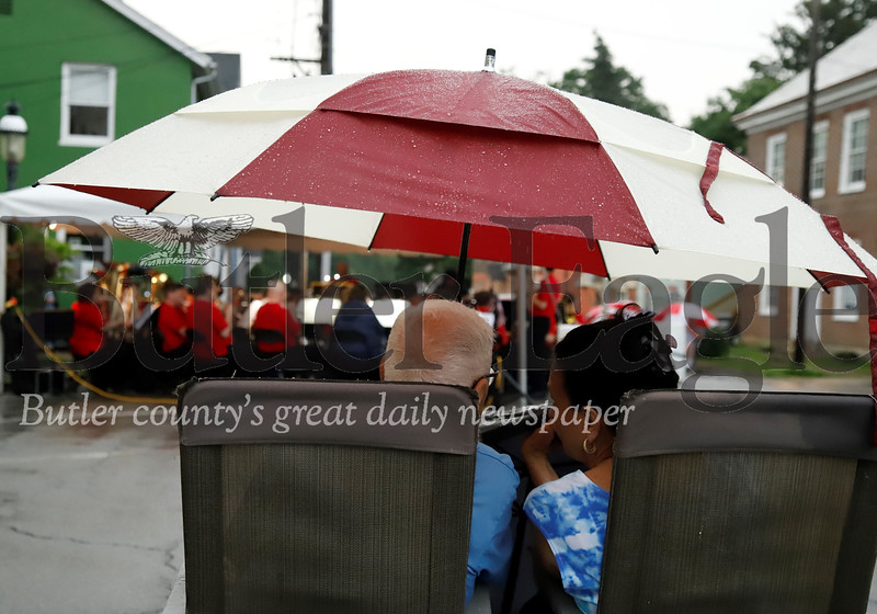 Clayton Buck of Butler and Karen Launer of Harmony don't let the rain get in the way of enjoying a live band as part of a wet Fourth of July celebration in Harmony Thursday. Seb Foltz/Butler Eagle