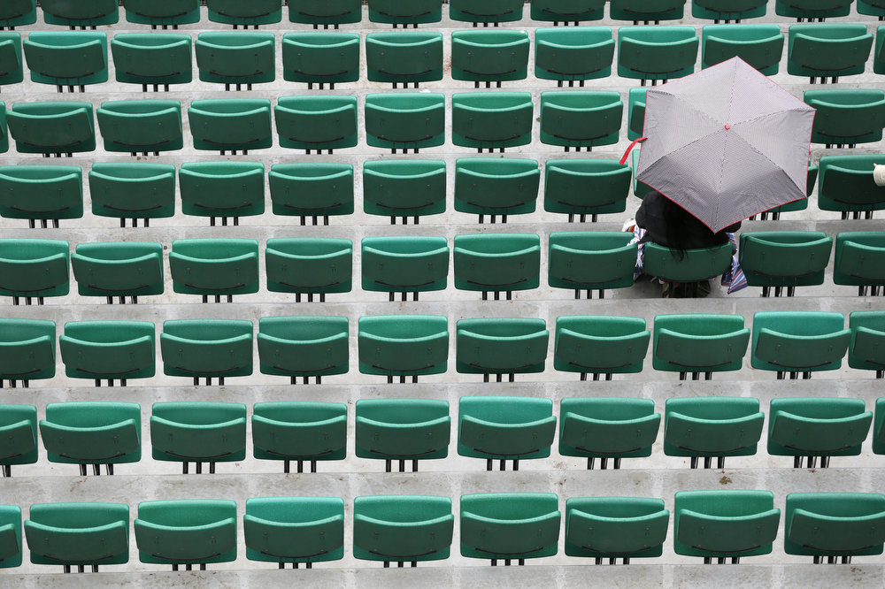 . A person sits in an empty tribune of the Philippe Chatrier central court as rain falls on the third day of the French tennis Open at the Roland Garros stadium in Paris on May 28, 2013. KENZO TRIBOUILLARD/AFP/Getty Images