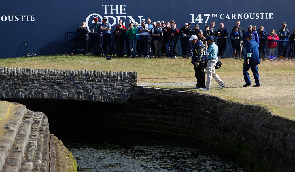 . Kevin Kisner of the US talks to officials after hitting the ball into the water on the 18th hole during the second round of the British Open Golf Championship in Carnoustie, Scotland, Friday July 20, 2018. (AP Photo/Alastair Grant)