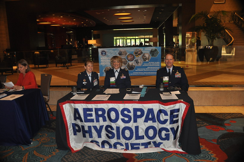 Manning the Aerospace Physiology Society table are Julie Sundstrom, Shawnee Williams, and Dana Thomas.