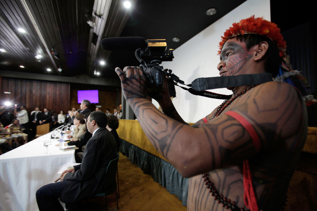 . An Indian from the Munduruku tribe films during a meeting with the government at the Planalto presidential palace in Brasilia, Brazil, Tuesday, June 4, 2013. The Indians, who had been occupying the controversial Belo Monte dam which is being built in the Amazon on the Xingu River, were flown to Brasilia by the government for talks to try to end the occupation. Environmentalists and indigenous groups say the dam would devastate wildlife and the livelihoods of thousands of people who live in the area to be flooded. (AP Photo/Eraldo Peres)