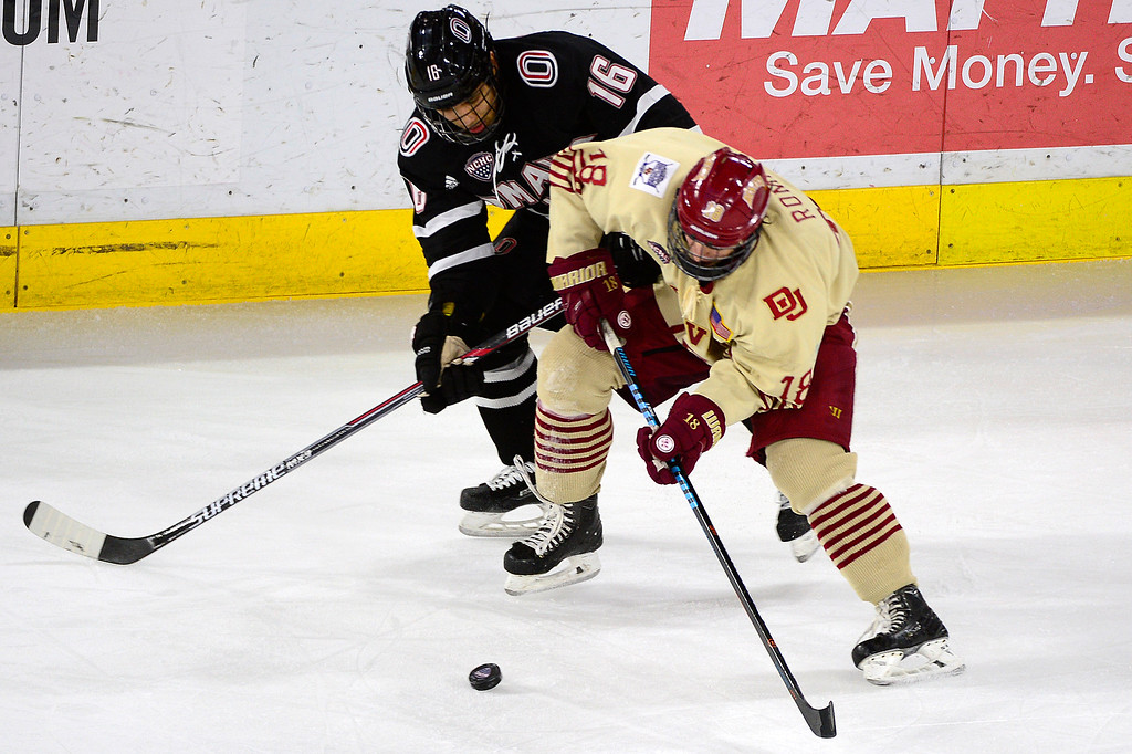 . Nebraska-Omaha Mavericks forward Austin Ortega (16) and Denver Pioneers forward Emil Romig (18) battle for control of the puck during the first period at Magness Arena on March 4, 2016 in Denver, Colorado. (Photo by Brent Lewis/The Denver Post)