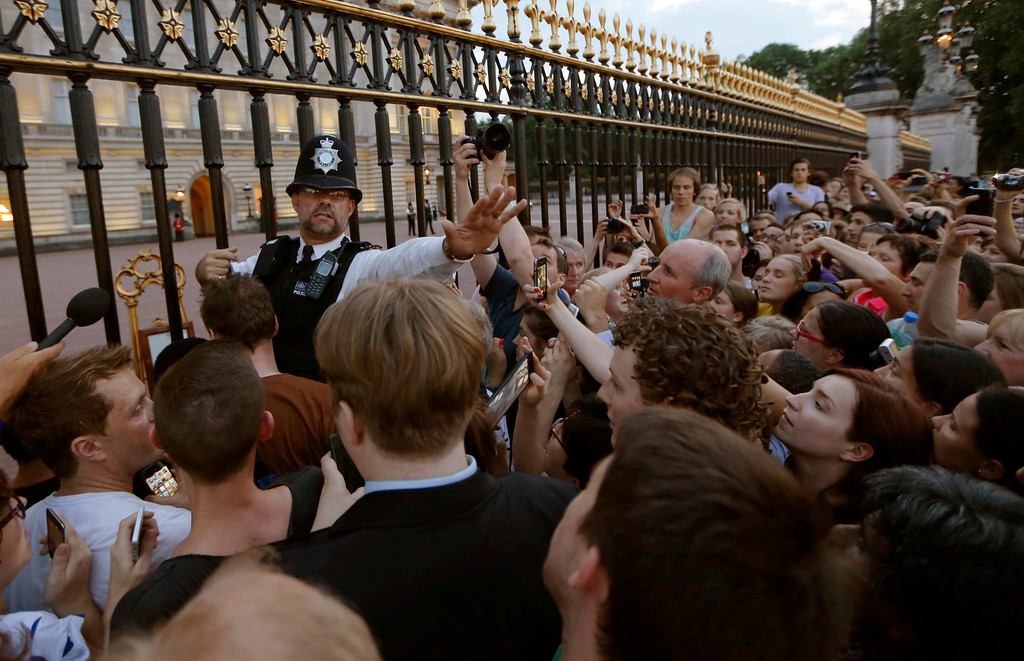 . A police officer tries to control a crowd of people trying to get to the railing to take pictures of a notice proclaiming the birth of a baby boy to Prince William and Kate, Duchess of Cambridge on display for  public view at Buckingham Palace in London, Monday, July 22, 2013. (AP Photo/Sang Tan)