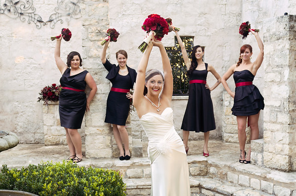 Bride and bridesmaids lifting bouquets in the air