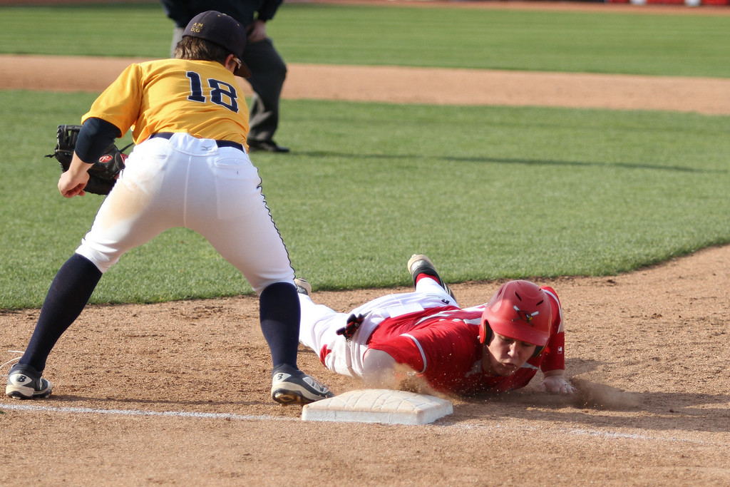 . Michael Johnson - The News-Herald Mentor\'s Tom Noll (right) beats the tag of Ignatius first baseman Tommy Grosel (left) during the Mentor vs. Ignatius baseball game at Classic Park on April 20, 2016.  Ignatius defeated Mentor 5-4.