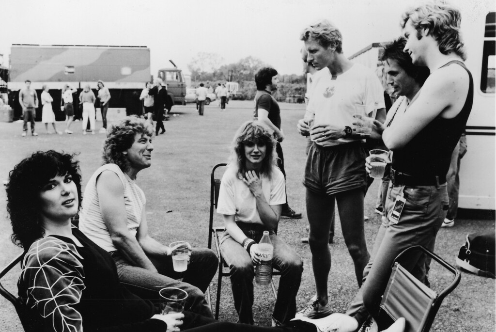 . British musician Robert Plant visits members of the rock group Heart after their performance in Milton Keynes, England, circa 1980s. (L-R) Ann Wilson, Robert Plant, Nancy Wilson, Marke Andes, Denny Carmassi and Howard Leese talk on the concert grounds. (Photo by Epic/Hulton Archive/Getty Images)