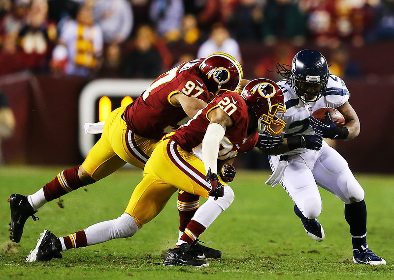. Cedric Griffin #20 and  Lorenzo Alexander #97 of the Washington Redskins tackle  Marshawn Lynch #24 of the Seattle Seahawks in the second quarter of the NFC Wild Card Playoff Game at FedExField on January 6, 2013 in Landover, Maryland.  (Photo by Al Bello/Getty Images)