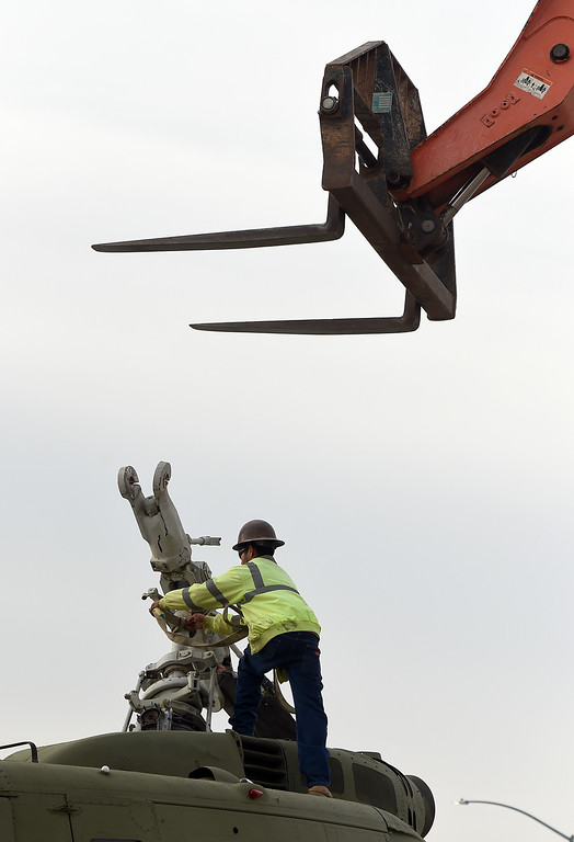 . Crews remove a movie prop military helicopter from the southbound lanes of the 15 freeway near Summit Ave in Fontana, CA, Friday, February 20, 2015. The copter fell off a flat bed trailer after hitting an over cross. (Jennifer Cappuccio Maher/Inland Valley Daily Bulletin)