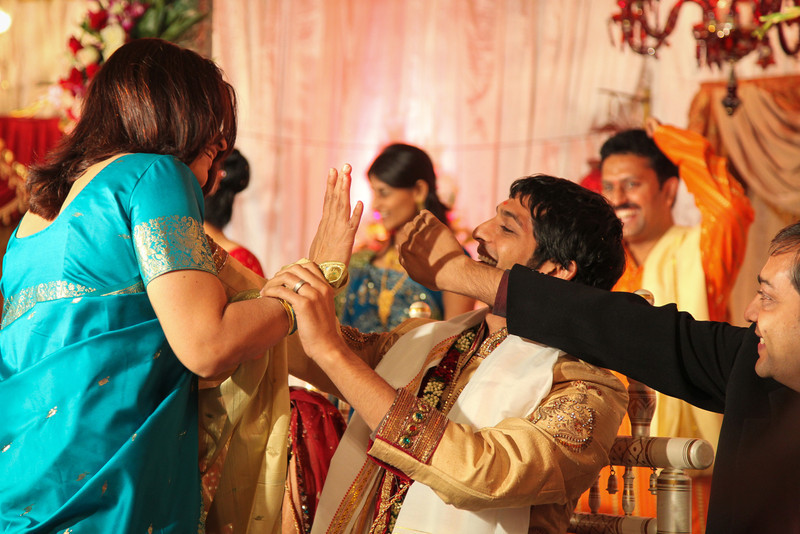 The groom avoids paint on his forehead so he can be presentable for photographs.