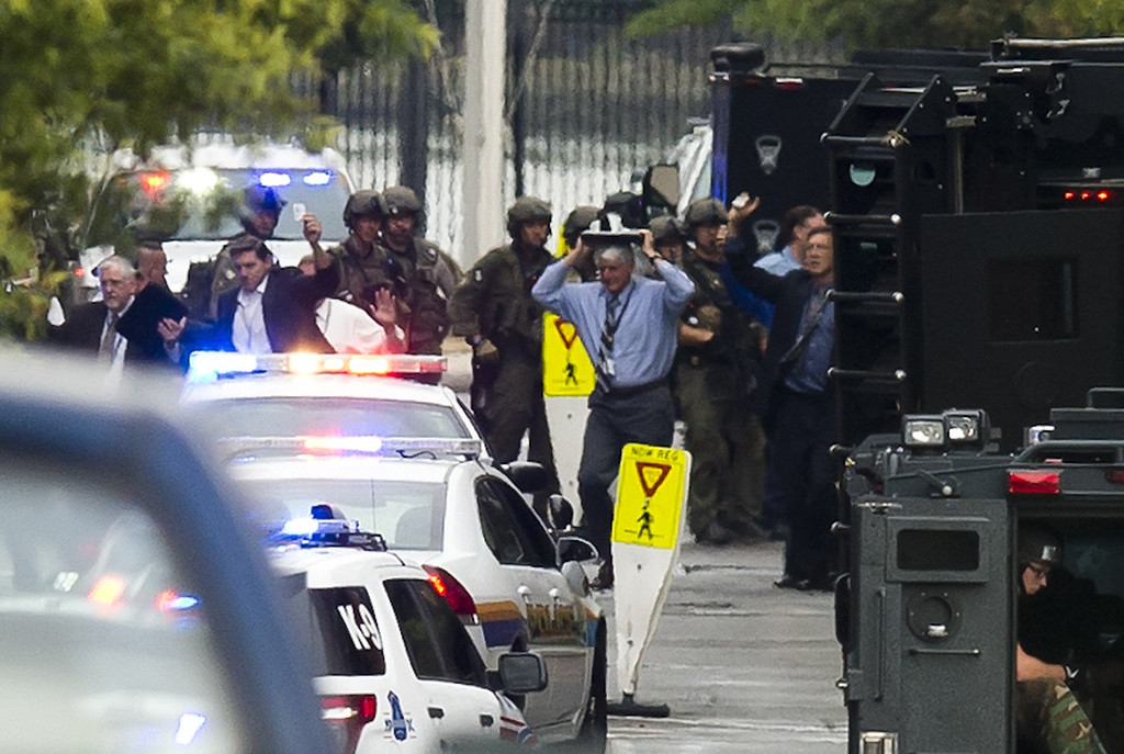 """. People exit a building with their hands above their heads as police respond to the report of a shooting at the Navy Yard in Washington, DC, September 16, 2013. At least one unidentified gunman opened fire at the US Navy Yard in Washington on Monday and was at large after killing \""""multiple\"""" victims and wounding several more, officials said. Police and FBI agents descended on the area in force as helicopters swarmed overhead, amid reports a shooter was armed with an assault rifle and was holed up at the complex. \""""We believe there were multiple deaths,\"""" a US defense official, speaking on condition of anonymity, told AFP. The precise death toll remained unclear, the official said. A Washington DC police officer and another law enforcement officer had been shot while the gunman had allegedly barricaded himself in a room in a headquarters building, media reported.   SAUL LOEB/AFP/Getty Images"""