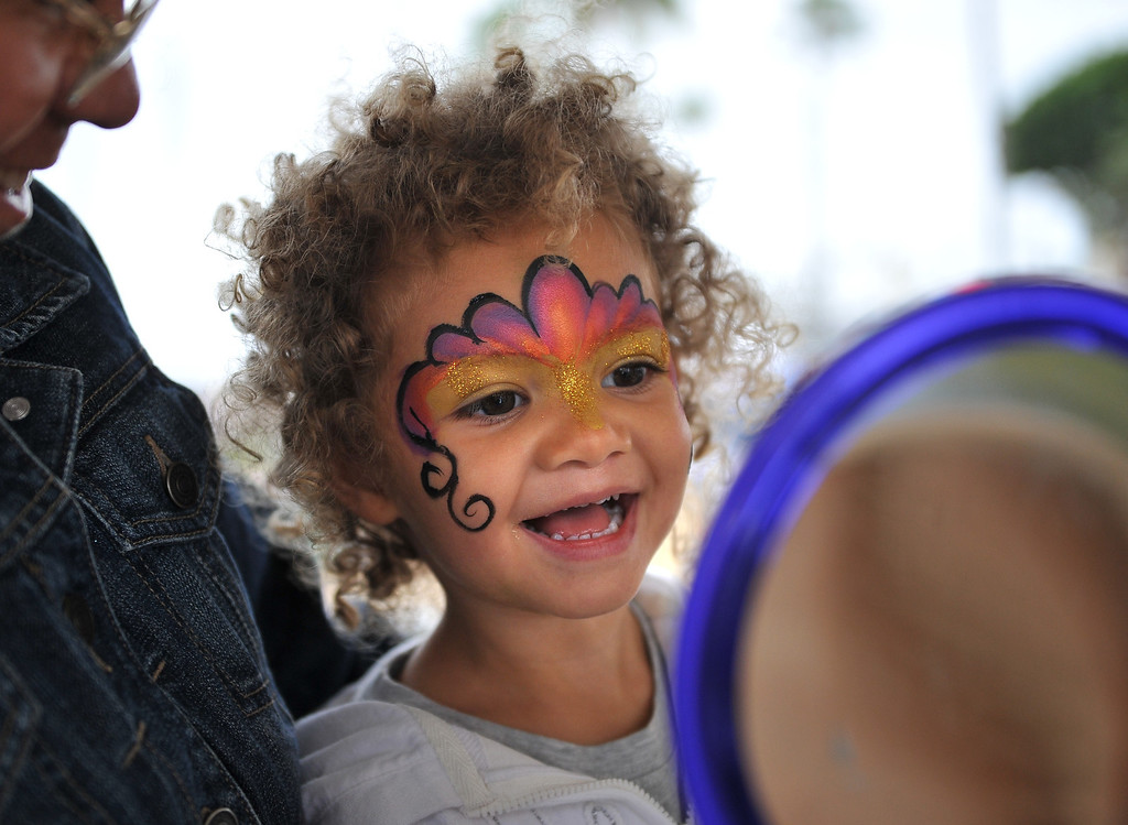 . 5/25/13 - Jordyn (CQ) Arellano, 2 1/2 reacts to her beautiful face paint before at the 10K at the Children Today\'s 5th Annual run/walk at Marina Green Park. The local non-profit, Children Today, is an organization that provides for families and children experiencing homelessness in Long Beach. They\'ve raised $33,184 and their final goal is $50,000. Photo by Brittany Murray / Staff Photographer