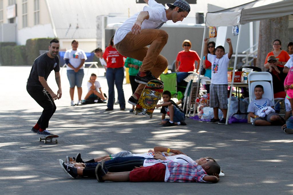 """. IDB-L-Pom-Campout-01 (Correspondent Photo by James Carbone) Professional skateboarders Shaun Hover, center, and Anthony Carney, \""""ollie\"""" over five kids during a skateboard demonstration, during the 2013 GREAT Camp Out, at the Park Square area at the Pomona Fairplex, in Pomona, Saturday, July 13, 2013. The Event organized by the Pomona Police Department provides an opportunity for kids to interact with police officers in a positive environment."""