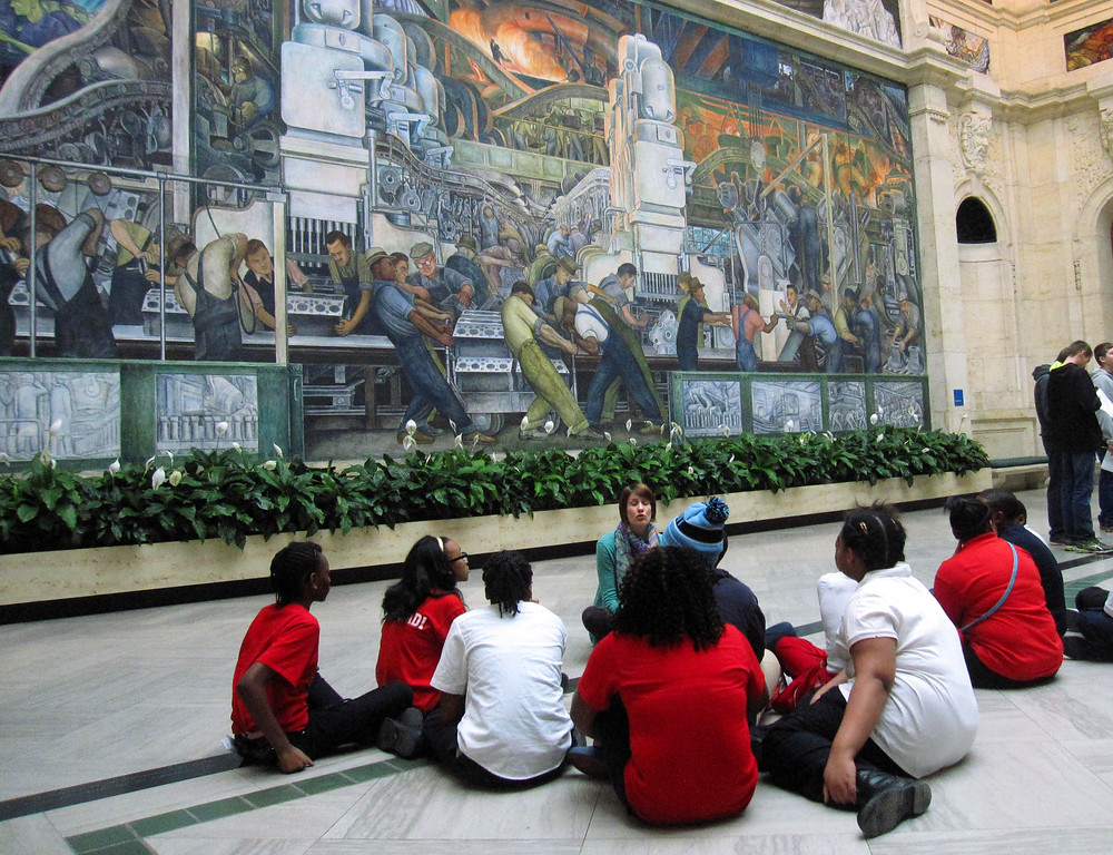 . This Dec. 5, 2014 photo shows a class learning about the Detroit Industry Murals at the Detroit Institute of Arts. The murals were done in the 1930s by Diego Rivera as a tribute to Detroit�s manufacturing industry, and  Rivera spent time studying the River Rouge Ford car factory. The museum�s collection was at one point threatened with a sale to help fund Detroit�s pension obligations, but finalization of the city�s bankruptcy last week included a deal that protects the art. (AP Photo/Beth J. Harpaz)