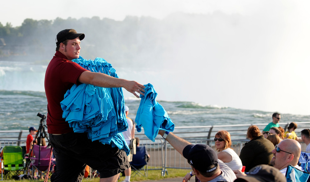 . A worker sells Nik Wallenda shirts in Niagara Falls, N.Y., Friday, June 15, 2012. Wallenda will attempt what nobody has done before: A high wire walk directly over the precipice at Niagara Falls and 190 feet (58 meters) above the churning torrent below. (AP Photo/Gary Wiepert)