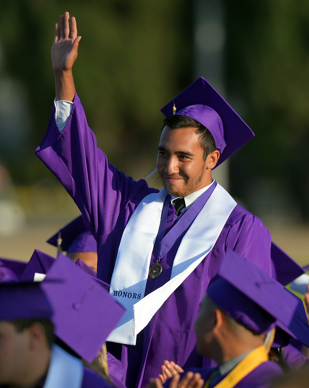 . Christian Rios waves after his mother, school board President Margarita Rios, singled him out during her speech. Norwalk High School\'s graduating class of 2014 goes through their commencement ceremony at Excelsior High School\' football stadium in Norwalk, CA on Tuesday, June 17, 2014. (Photo by Scott Varley, Daily Breeze)