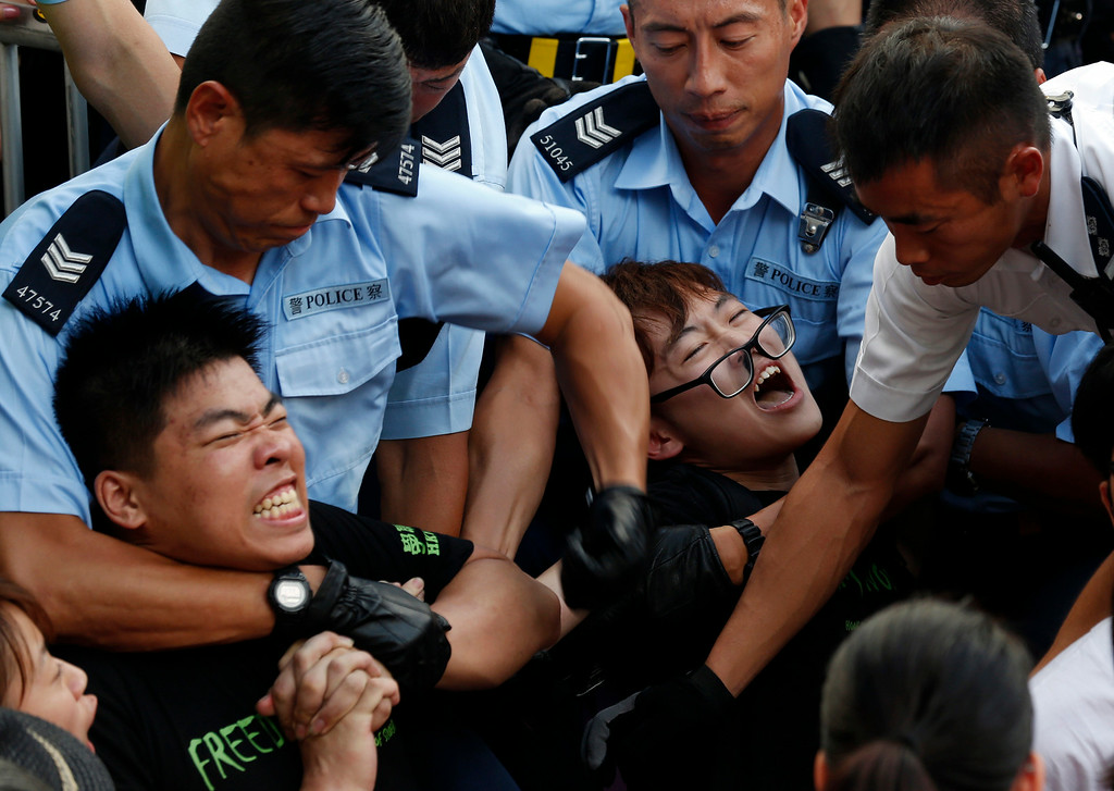 . Protesters are taken away by police officers after hundreds of protesters staged a peaceful sit-ins overnight on a street in the financial district in Hong Kong Wednesday, July 2, 2014, following a huge rally to show their support for democratic reform and oppose Beijing\'s desire to have the final say on candidates for the chief executive\'s job. (AP Photo/Kin Cheung)