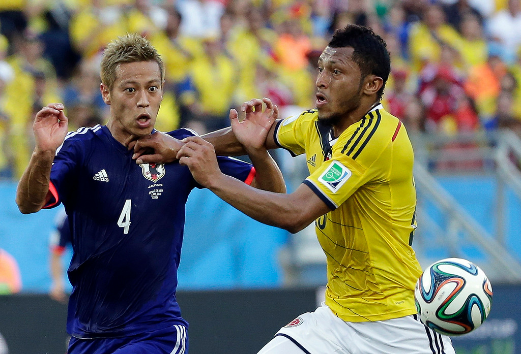 . Japan\'s Keisuke Honda, left, and Colombia\'s Carlos Valdes fight for the ball during the group C World Cup soccer match between Japan and Colombia at the Arena Pantanal in Cuiaba, Brazil, Tuesday, June 24, 2014. (AP Photo/Felipe Dana)