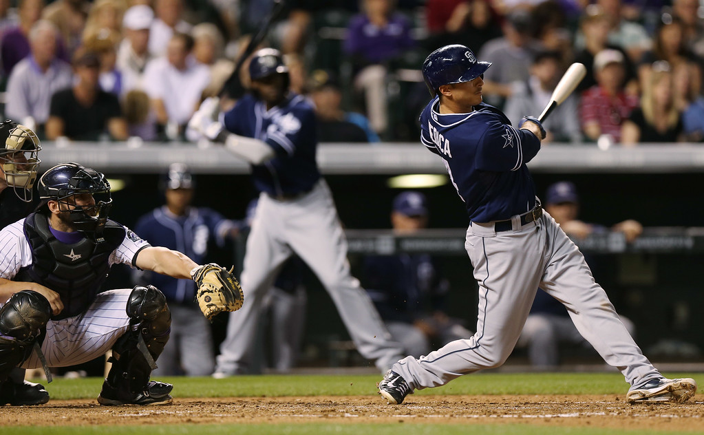 . San Diego Padres\' Tommy Medica, right, follows the flight of his solo home run as Colorado Rockies catcher Michael McKenry looks on in the fifth inning of a baseball game in Denver on Saturday, Sept. 6, 2014. (AP Photo/David Zalubowski)