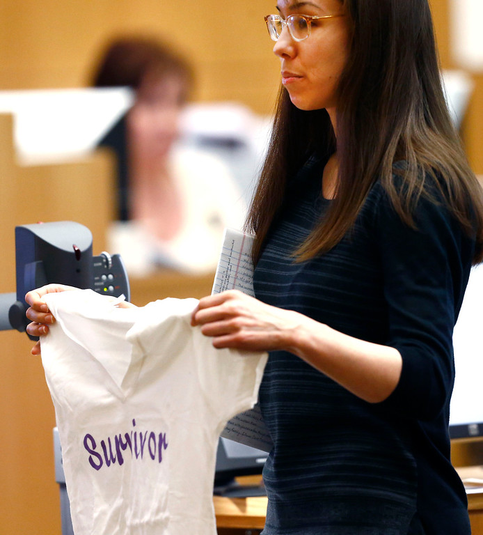 ". Jodi Arias holds-up a ""Survivor\"" T-shirt as she addresses the jury on Tuesday, May 21, 2013 during the penalty phase of her murder trial at Maricopa County Superior Court in Phoenix.  Arias was convicted of first-degree murder in the stabbing and shooting to death of Travis Alexander. (AP Photo/The Arizona Republic, Rob Schumacher, Pool)"