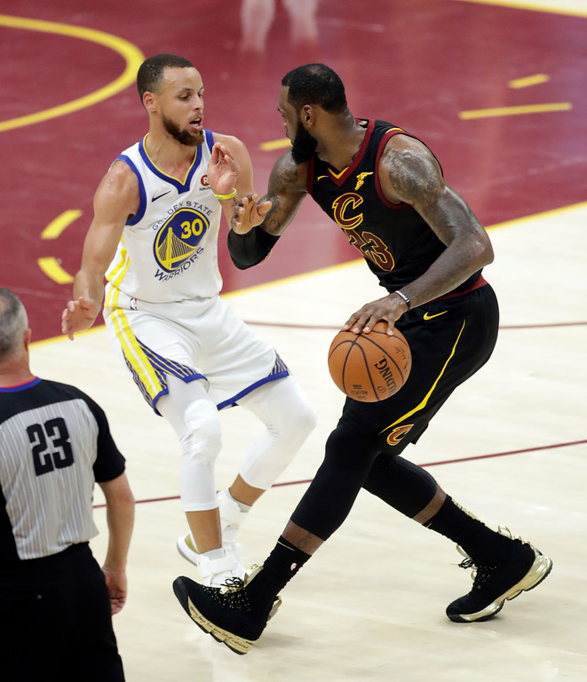 . Golden State Warriors\' Stephen Curry defends against Cleveland Cavaliers\' LeBron James during the first half of Game 4 of basketball\'s NBA Finals, Friday, June 8, 2018, in Cleveland. (AP Photo/Tony Dejak)