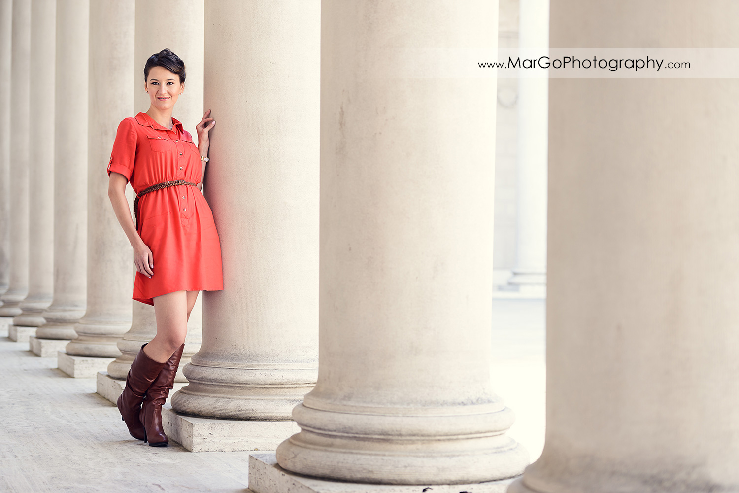 full body portrait of woman in red dress standing next to white columns during engagement session at San Francisco Legion of Honor