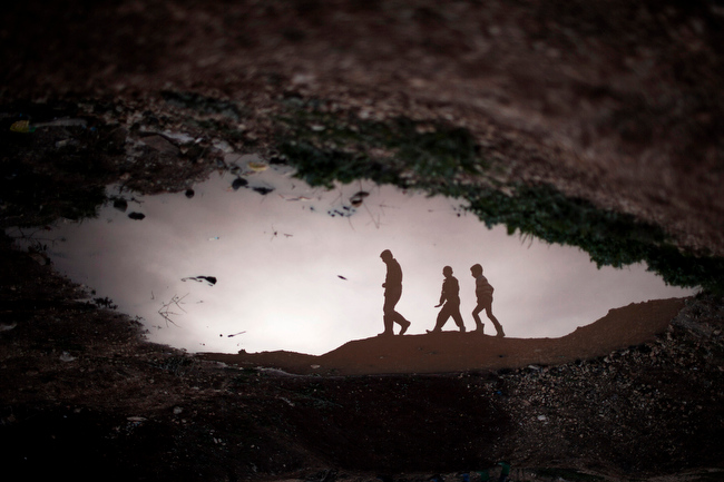 Description of . Displaced Syrian children are reflected in a puddle as they walk through an olive tree field near the Azaz camp for displaced people, north of Aleppo province, Syria, Thursday, Feb. 21, 2013. According to Syrian activists the number of people in the Azaz camp has grown by 3,000 in the last weeks due to heavier shelling by government forces. (AP Photo/Manu Brabo)