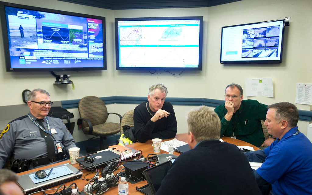 . Virginia Gov. Terry McAuliffe, second from left, listens to Secretary of Public Safety, Brian Moran, front center, with back to camera, Superintendent of State Police, Col. Steven Flaherty, left, Chief of Staff Paul Regan, second from right, and Virginia coordinator of Emergency management, Jeff Stern, right, in the Emergency Operation Center in Richmond, Va., Saturday, Jan. 23, 2016. Portions of Virginia are under a blizzard warning. (AP Photo/Steve Helber)