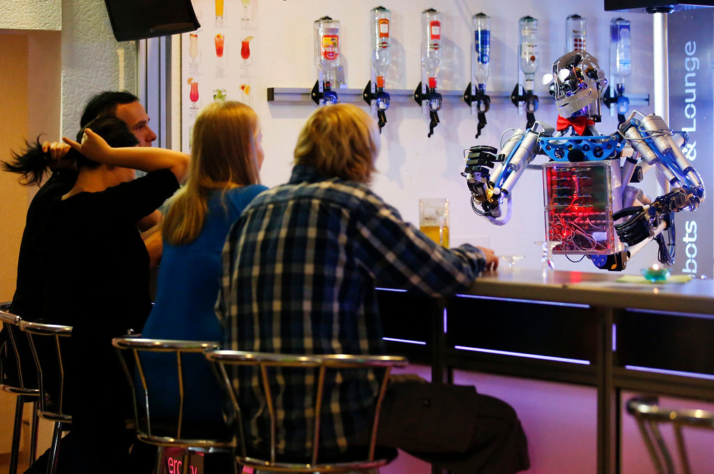 ". Humanoid robot bartender ""Carl\"" gestures to guests at the Robots Bar and Lounge in the eastern German town of Ilmenau, July 26, 2013. \""Carl\"", developed and built by mechatronics engineer Ben Schaefer who runs a company for humanoid robots, prepares spirits for the mixing of cocktails and is able to interact with customers in small conversations. Picture taken July 26, 2013. REUTERS/Fabrizio Bensch"