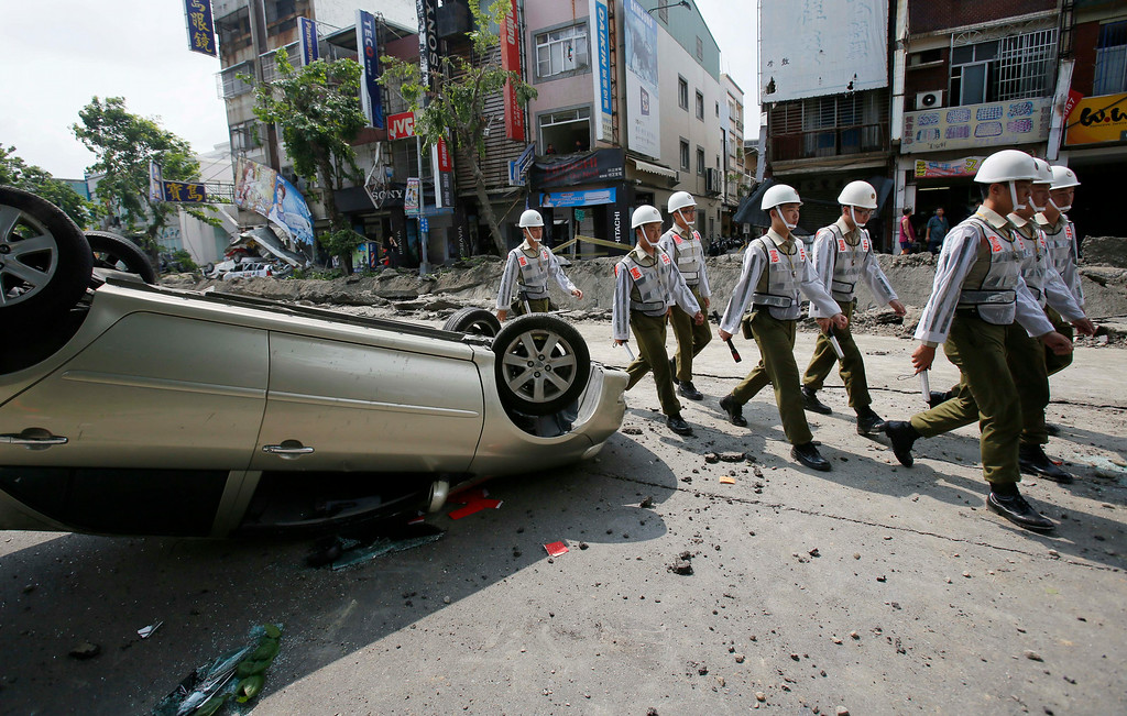 . Soldiers walk through a street destroyed by a massive gas explosion in Kaohsiung, Taiwan, Friday, Aug. 1, 2014. Scores of people were killed and more than 200 others injured when several underground gas explosions ripped through Taiwan\'s second-largest city overnight, hurling concrete through the air and blasting long trenches in the streets, authorities said Friday. (AP Photo/Wally Santana)