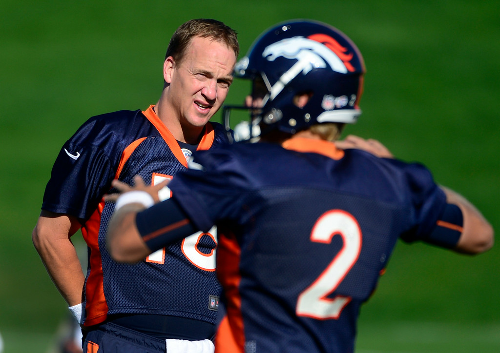 . Quarterback Peyton Manning, left, gets a glimpse of fellow QB Zac Dysert at the start of practice. The Denver Broncos football team gets in their final day of practice during training camp at Dove Valley on Friday, Aug. 15, 2014. (Photo by Kathryn Scott Osler/The Denver Post)