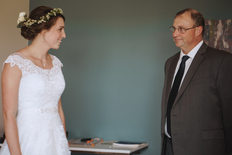 Bride and her father smiling at each other.