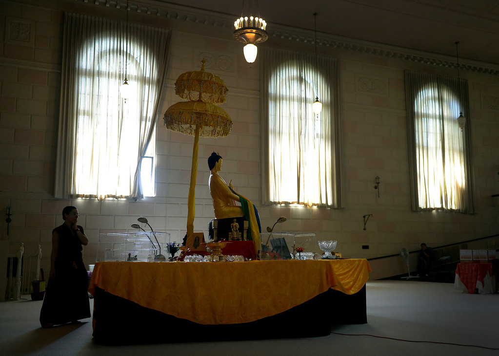. Venerable Norbu, a Buddhist nun, prepares the alter around the Maitreya Buddha at the Zen Center of Denver in Denver, CO August 23, 2013. (Photo By Craig F. Walker / The Denver Post)