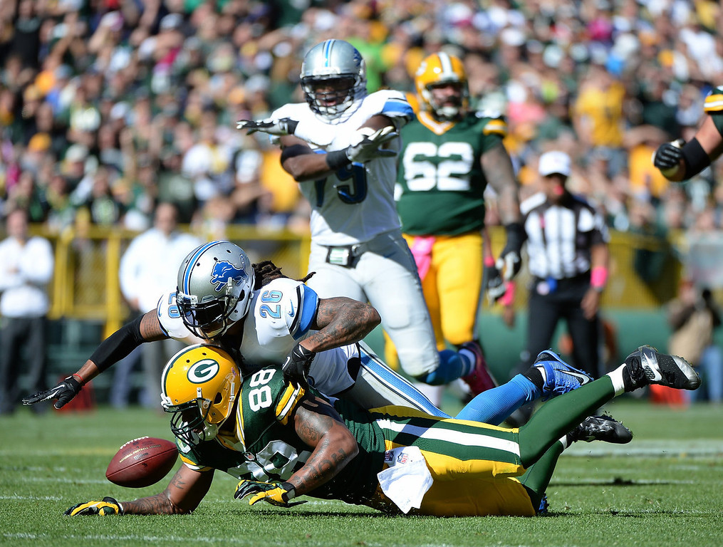. Jermichael Finley #88 of the Green Bay Packers has the ball knocked out of his hands by Louis Delmas #26 of the Detroit Lions during the first quarter t Lambeau Field on October 6, 2013 in Green Bay, Wisconsin.  (Photo by Harry How/Getty Images)