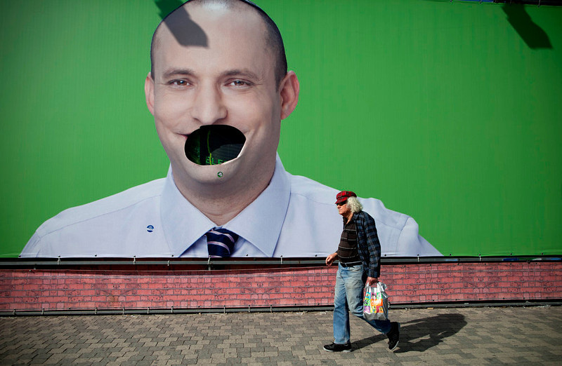 . An Israeli man walk past a vandalized election campaign billboard of Naftali Bennett, head of the Jewish Home party, in Tel Aviv, Israel, Sunday, Jan. 20, 2013. General elections in Israel are scheduled for Jan. 22, 2013. (AP Photo/Oded Balilty)