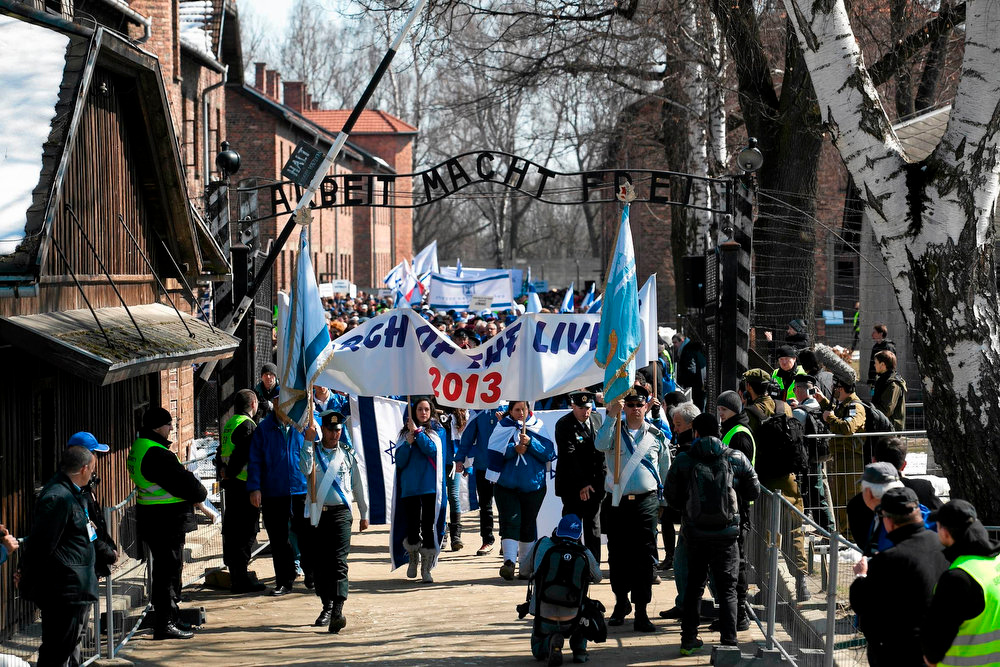 ". People walk through the gate, with the words ""Arbeit Macht Frei\"" (Work sets you free), of the former Nazi death camp of Auschwitz in Oswiecim, southern Poland April 8, 2013. Thousands of mainly Jewish people participated in the 22nd annual \""March of the Living\"", a Holocaust commemoration. REUTERS/Jakub Ociepa/Agencja Gazeta"