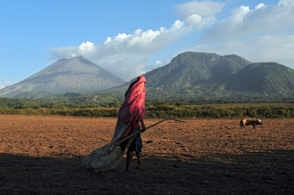Description of . A man walks in a field in Grecia 4, Chinandega, 150 km from Managua, with the San Cristobal volcano in the background on December 26, 2012. The San Cristobal volcano began spewing smoke and ashes Tuesday afternoon. HECTOR RETAMAL/AFP/Getty Images