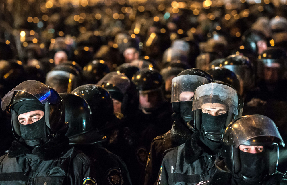""". Riot policemen wait prior to launch an assault on a  barricade held by protesters on Independence Square  in Kiev late on December 11, 2013. Ukrainian security forces on Wednesday stormed Kiev\'s Independence Square which protesters have occupied for over a week but the demonstrators defiantly refused to leave and resisted the police in a tense standoff. Eite Berkut anti-riot police and interior ministry special forces moved against the protestors at around 2:00 am (midnight GMT) in a move that prompted US Secretary of State John Kerry to express \""""disgust\"""" over the crackdown. DMITRY SEREBRYAKOV/AFP/Getty Images"""