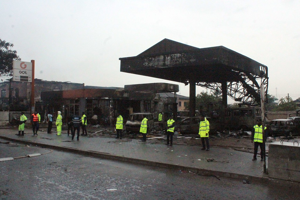 . Policemen stand guard as rescuers work on the site where at least 90 people were killed in a petrol station fire in Ghana\'s capital, Accra, on June 4, 2015. The fire broke out at the filling station in the Kwame Nkrumah Circle area of the city late on Wednesday night and is thought to have spread from a nearby residence. AFP PHOTO / FATI  BRAIMAH/AFP/Getty Images