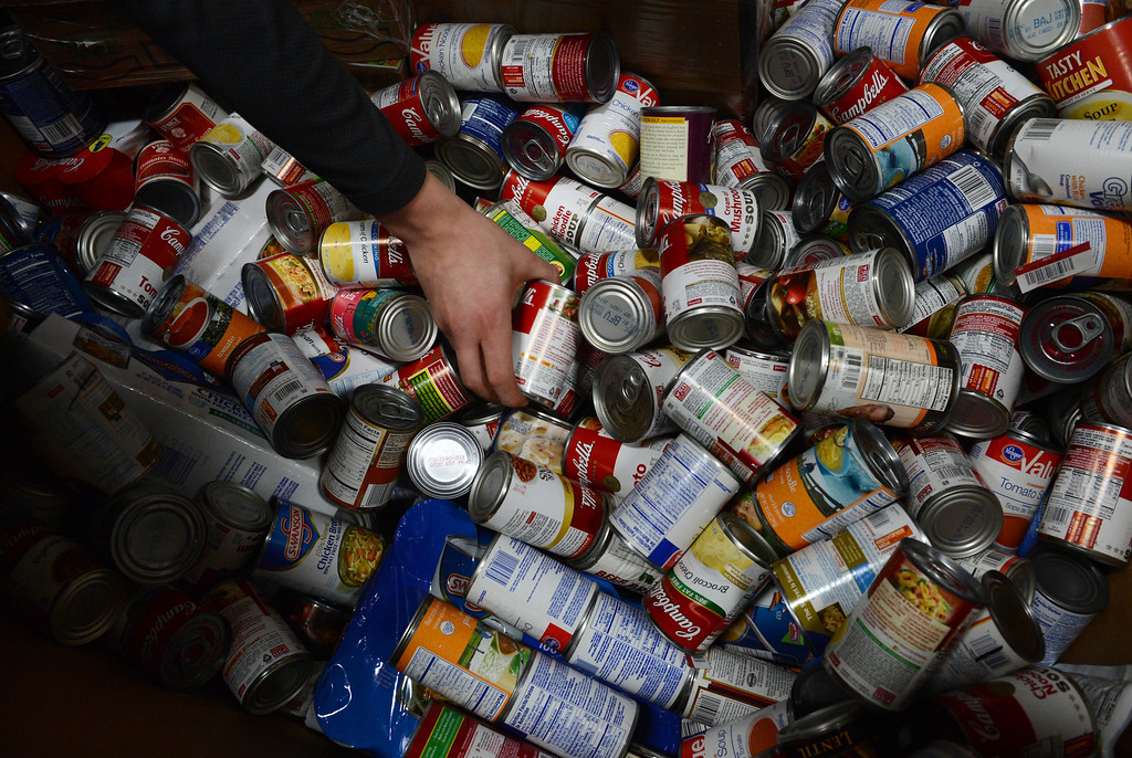 . Volunteer Hunter McClure sorts donated soup at the Community Food Share in Longmont, CO, Thursday December 27, 2012.   Craig F. Walker, The Denver Post