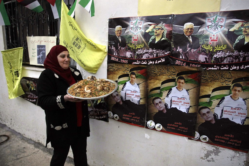 ". A Palestinian relative of Ibrahim Taqtoq, carries a dish with chicken and rice as she walks past posters of Palestinian President Mahmoud Abbas and late Palestinian leader Yasser Arafat with Arabic that reads, ""Fatah, struggling and building,\"" top, and \""prisoner Samir Al-Naanish, prisoner Ibrahim Taqtoq,\"" bottom, in the West Bank city of Nablus, Monday, Dec. 30, 2013. Israel and the Palestinians are gearing up for the expected release by Israel of 26 of the longest-serving Palestinian prisoners. Israel has agreed to release the men, who were all convicted in deadly attacks of Israelis, as part of a U.S.-brokered package to restart peace talks. (AP Photo /Nasser Ishtayeh)"