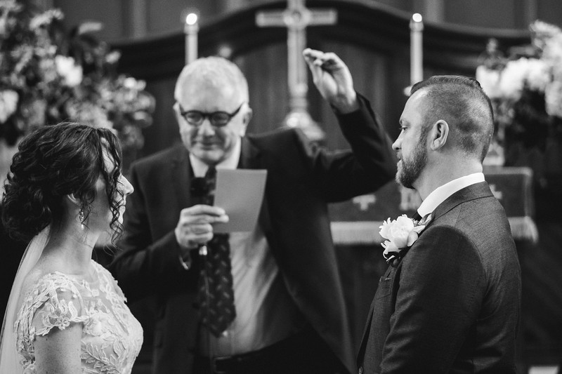 The bride and groom facing each other as the reverend holds a ring up in the background.