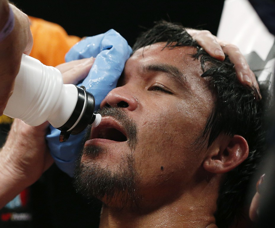 . Manny Pacquiao, from the Philippines, is assisted in his corner during his welterweight title fight against Floyd Mayweather Jr. on Saturday, May 2, 2015 in Las Vegas. (AP Photo/John Locher)