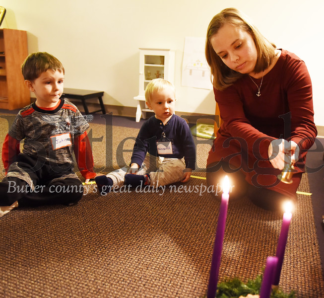 Harold Aughton/Butler Eagle: Amanda Kramer, coordinator of education for St. Fidelis of Sigmaringen Parish, lights the Advent candles while brothers John, 4, (left) and Athanasius Stanish watch.