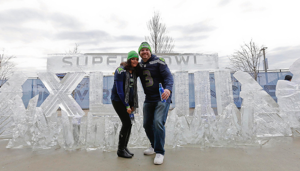 . Seattle Seahawks fans Aaron Hulet, right, and Erica Hulet, pose for a picture in front of an ice sculpture before the NFL Super Bowl XLVIII football game between the Seattle Seahawks and the Denver Broncos Sunday, Feb. 2, 2014, in East Rutherford, N.J. (AP Photo/Matt York)