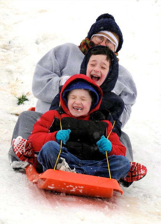 . While blizzard conditions made travel difficult, (front to back) John Michael Randolph, 6 years-old, Brecken Randolph, 9 years-old, and Kristie Randolph took advantage of the snow to go sledding at Atkinson Park in Henderson, Ky., Wednesday, Dec. 26, 2012. (AP Photo/The Gleaner, Mike Lawrence)