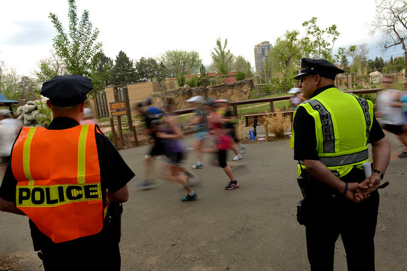 . Denver Police patrolmen Matt Church, left, and Toby Wilson, right, keep watch as runners run through the Denver Zoo as part of the Colfax Half Marathon in Denver, CO on May 19, 2013.  The Colfax Marathon, the  Half Marathon and the Urban Ten- Miler were held in City Park in Denver, CO on May 19th, 2013. The popular running events, sponsored by Kaiser Permanente, were sold out and thousands of runners took part in all three races.  Temperatures were cool with cloudy skies making for record setting times on both the Marathon and the half marathon by the winners.  (Photo by Helen H. Richardson/The Denver Post)