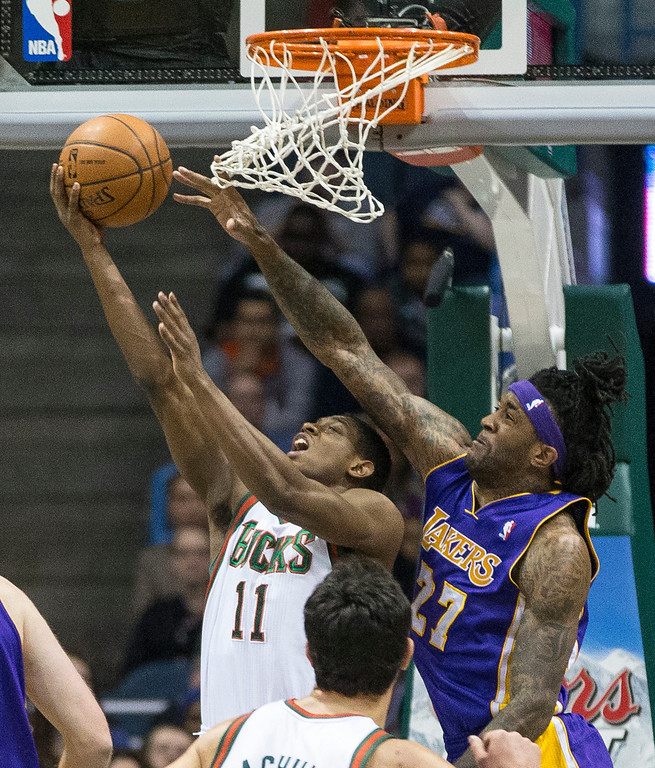 . Milwaukee Bucks\' Brandon Knight shoots a reverse lay-up as Los Angeles Lakers\' Jordan Hill defends during the first half of an NBA basketball game Thursday, March 27, 2014, in Milwaukee. (AP Photo/Tom Lynn)