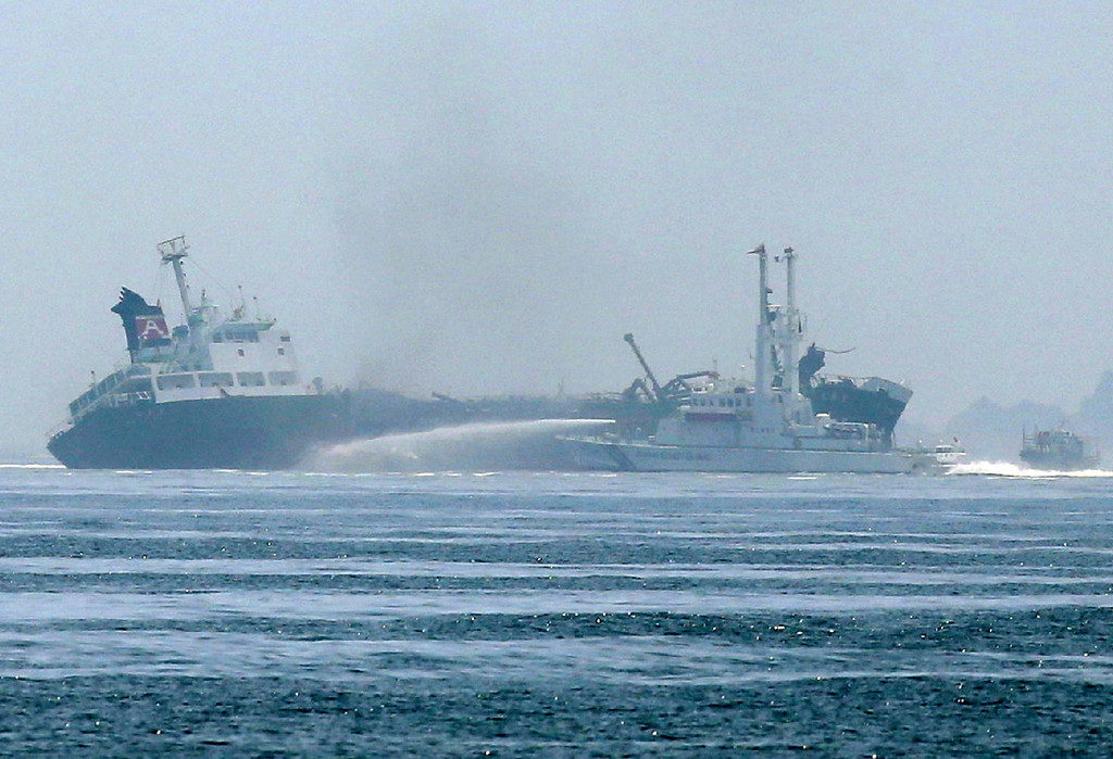 . This picture shows the 998 ton oil tanker Shoko-Maru (L) listing off the coast of Hyogo prefecture, around 450 kilometers (280 miles) west of Tokyo on May 29, 2014. A 998 ton oil tanker was listing off the Japanese coast on May 29 after an explosion and subsequent fire that sent towering columns of acrid smoke into the sky.   AFP PHOTO / JIJI PRESS     /AFP/Getty Images
