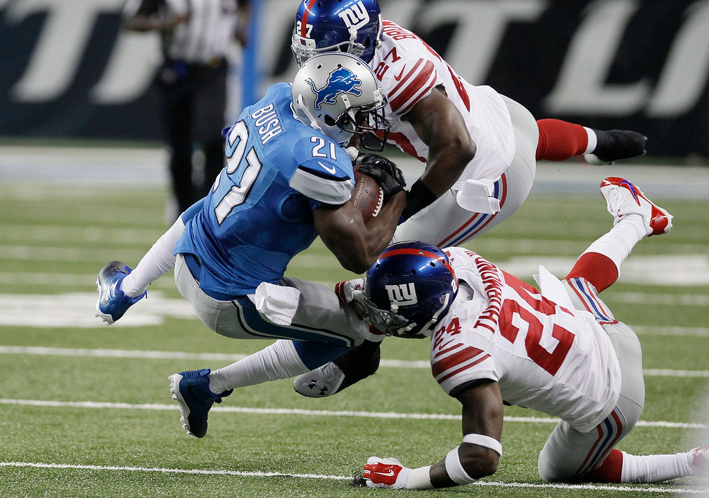 . Detroit Lions running back Reggie Bush is tackled by New York Giants strong safety Stevie Brown (27) and cornerback Walter Thurmond (24) during the first quarter of an NFL football game in Detroit, Monday, Sept. 8, 2014. (AP Photo/Duane Burleson)