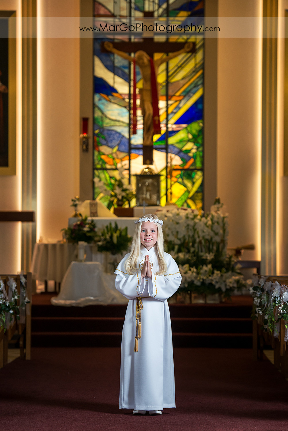 first communion girl in white alb with folded hands standing in front of the San Jose church altar